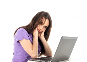 IMAGE - woman sitting uncomfortable at desk with laptop